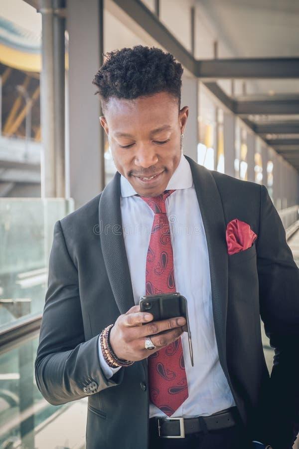 Il giovane uomo d'affari sta su fuori dell'aeroporto che esamina il Th fotografie stock libere da diritti