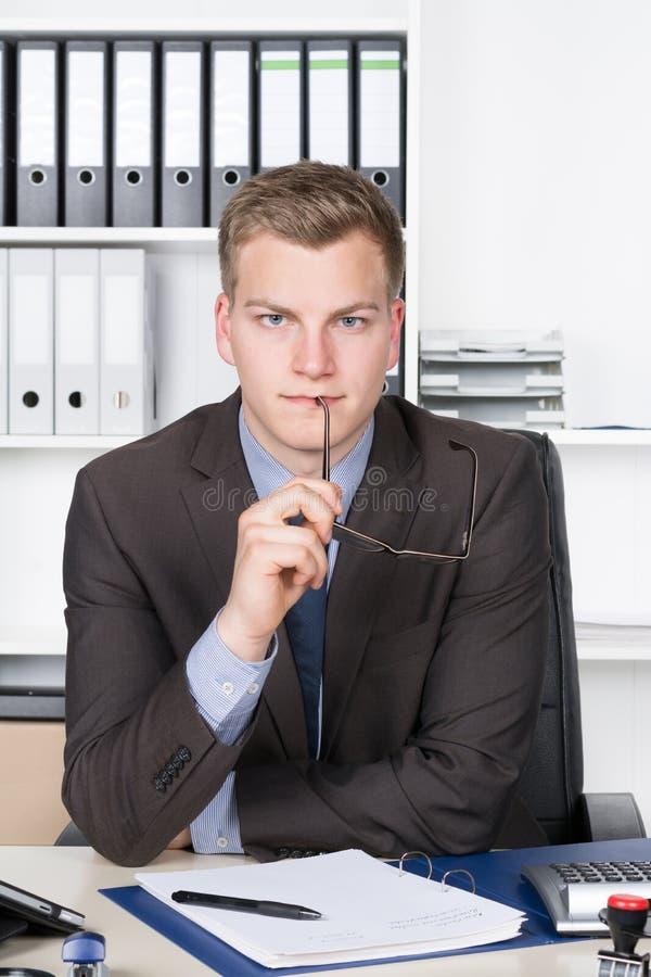 Il giovane uomo d'affari sta tenendo i suoi vetri alla sua bocca immagini stock libere da diritti