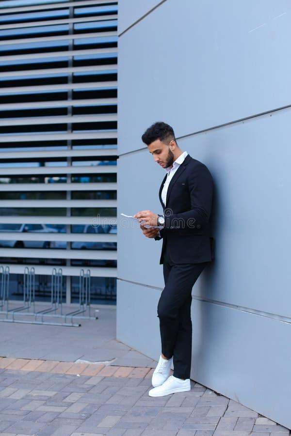 Il giovane uomo d'affari tiene ed esamina le carte, sta la parete vicina di fotografia stock libera da diritti