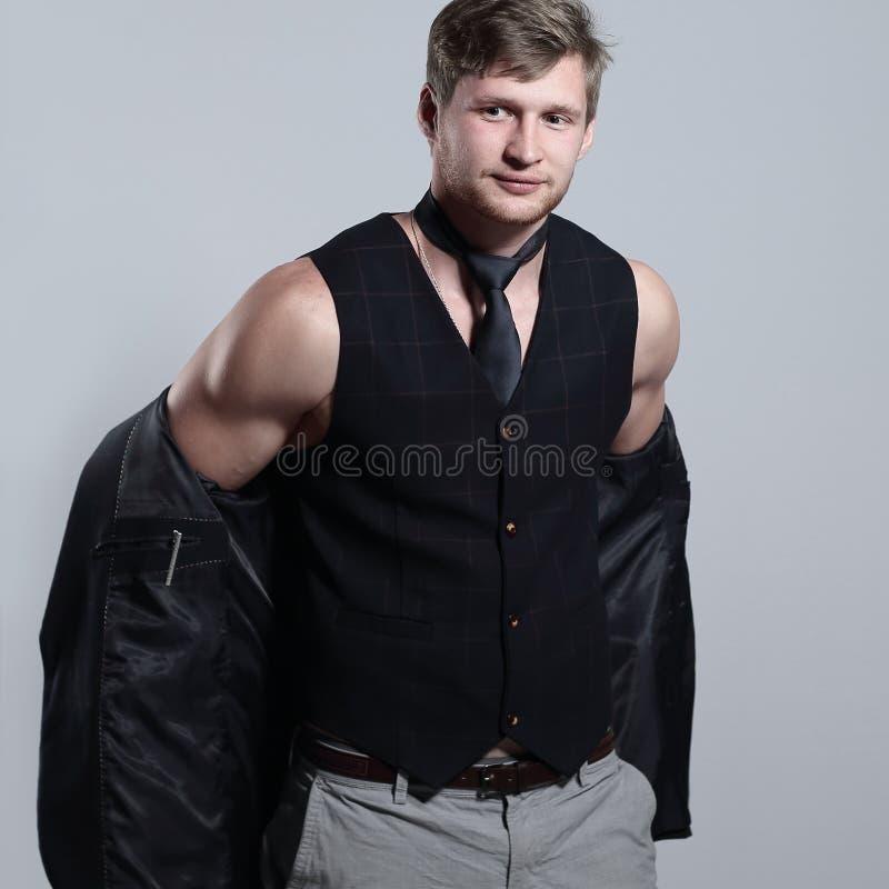 Il giovane uomo d'affari in un vestito senza una camicia tiene un rivestimento sopra la sua spalla immagine stock libera da diritti