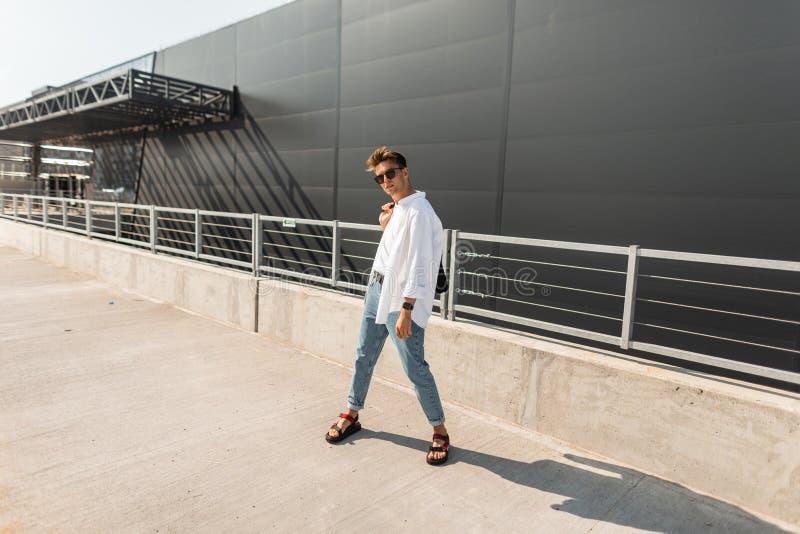 Il giovane uomo dei pantaloni a vita bassa in una camicia alla moda bianca in jeans alla moda blu in sandali d'annata dell'estate fotografie stock libere da diritti