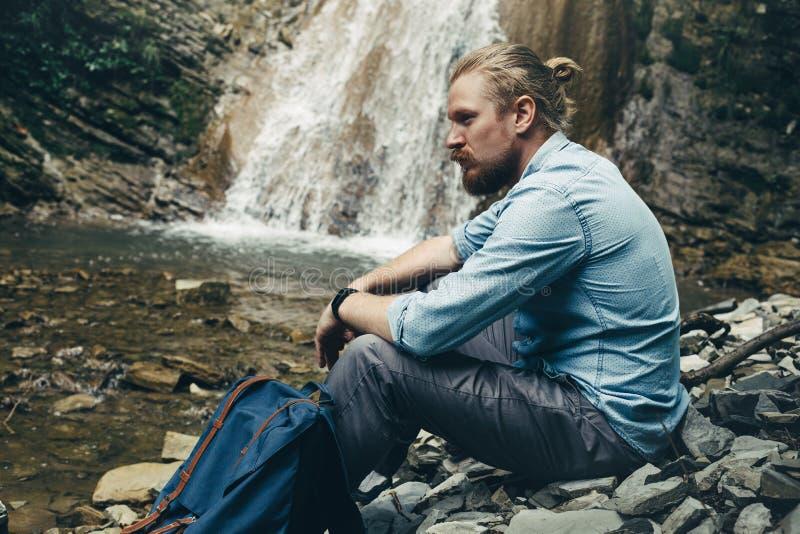 Il giovane uomo della viandante con lo zaino, sedentesi sulle rocce si avvicina al viaggio della cascata che fa un'escursione il  immagine stock