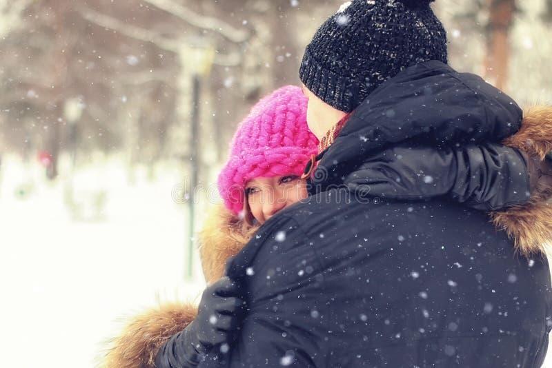 Il giovane uomo delle coppie porta un inverno della ragazza fotografie stock