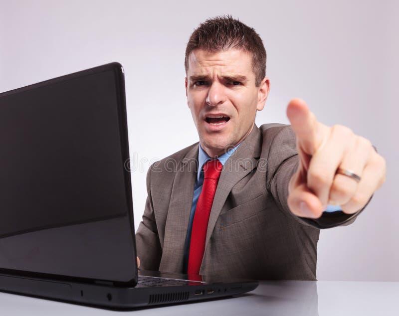 Il giovane uomo di affari indica voi dal suo computer portatile fotografia stock