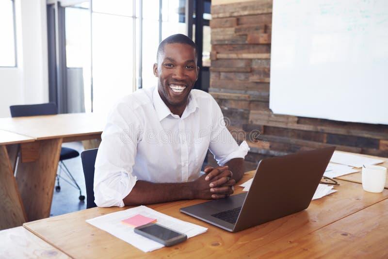 Il giovane uomo di colore allo scrittorio con il computer portatile guarda alla macchina fotografica immagine stock