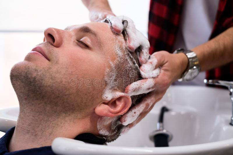 Il giovane uomo di Mcaucasian sta rilassandosi in parrucchiere durante il taglio di capelli fotografie stock libere da diritti