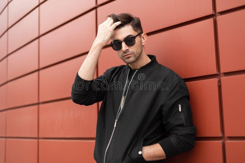 Il giovane uomo di modello alla moda bello in occhiali da sole raddrizza i suoi capelli Il tipo bello in rivestimento d'avanguard fotografie stock libere da diritti