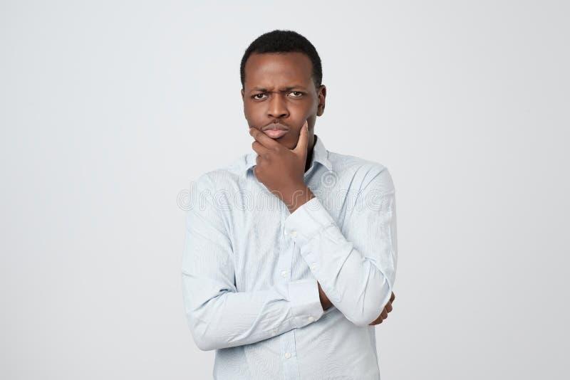 Il giovane uomo di pensiero africano cerca con la mano vicino al fronte isolato su fondo bianco immagini stock