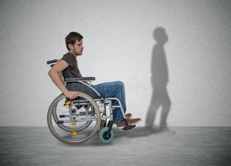 Il giovane uomo disabile sulla sedia a rotelle ha speranza per il recupero La sua ombra sta camminando vicino fotografie stock