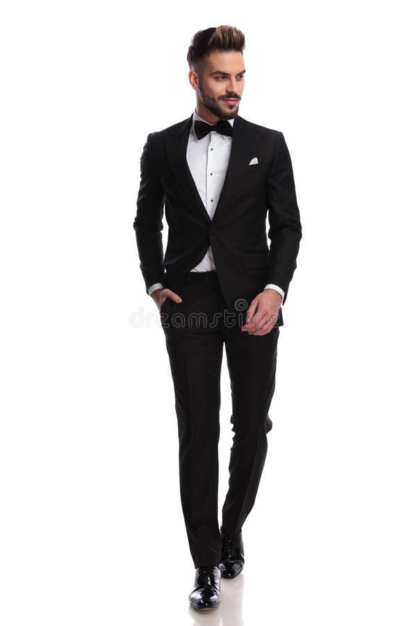 Il giovane uomo elegante sorridente sta camminando e guarda per parteggiare fotografie stock libere da diritti