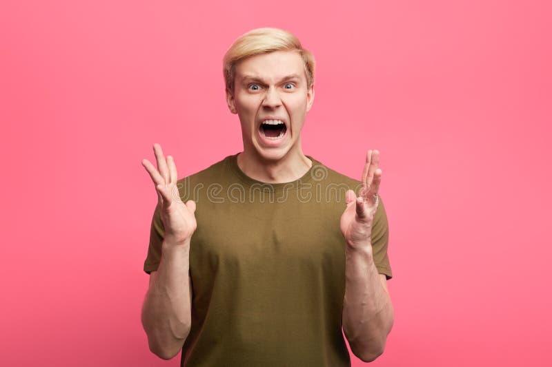 Il giovane uomo emozionale con l'espressione aggressiva e le armi si sono alzati fotografie stock libere da diritti
