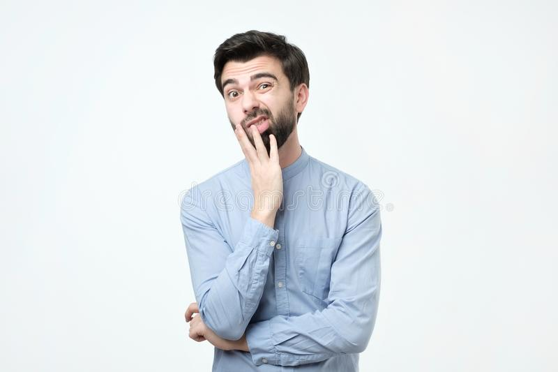 Il giovane uomo europeo in camicia blu pensa, guarda da parte a parte incredulously fotografie stock libere da diritti