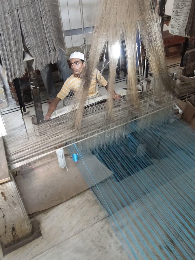Il giovane uomo musulmano esegue un telaio per tessere il broccato di seta fotografia stock