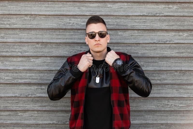 Il giovane uomo piacevole dei pantaloni a vita bassa in un rivestimento alla moda del plaid in una maglietta nera con gli occhial fotografia stock