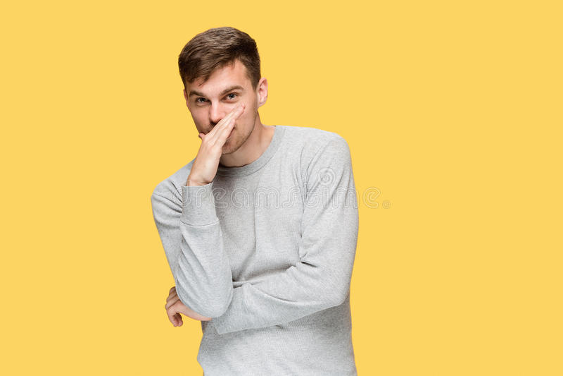 Il giovane uomo serio che guardano prudentemente e segreto parlante fotografie stock
