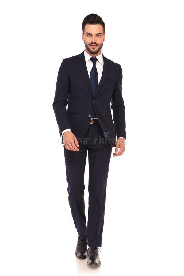 Il giovane uomo sorridente di affari sta camminando in avanti immagine stock libera da diritti