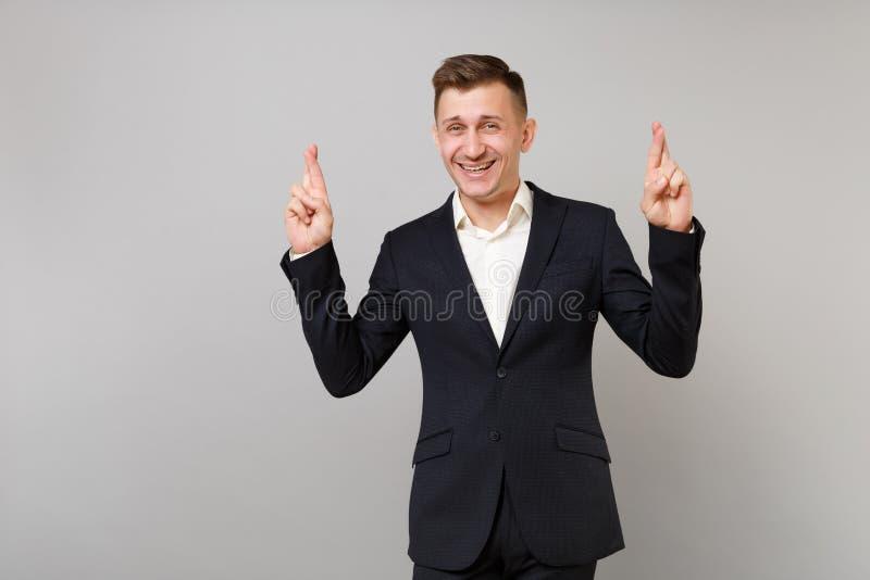 Il giovane uomo sorridente di affari in vestito classico che tiene le dita ha attraversato, aspettando il momento speciale, facen fotografia stock libera da diritti