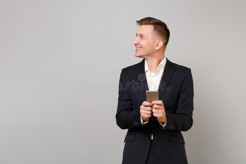 Il giovane uomo sorridente di affari in vestito nero classico, camicia che guarda da parte facendo uso del messaggio di battitura fotografie stock libere da diritti