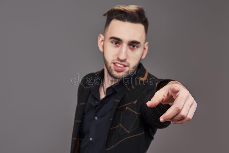 Il giovane uomo sorridente nell'usura convenzionale che indica con il dito su voi, esaminando la macchina fotografica, ha isolato immagini stock libere da diritti