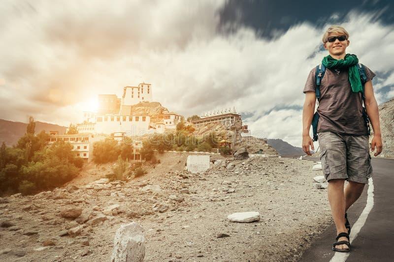 Il giovane uomo turistico cammina sulla strada vicino al monastero di Thiksey in India, Ladakh immagini stock