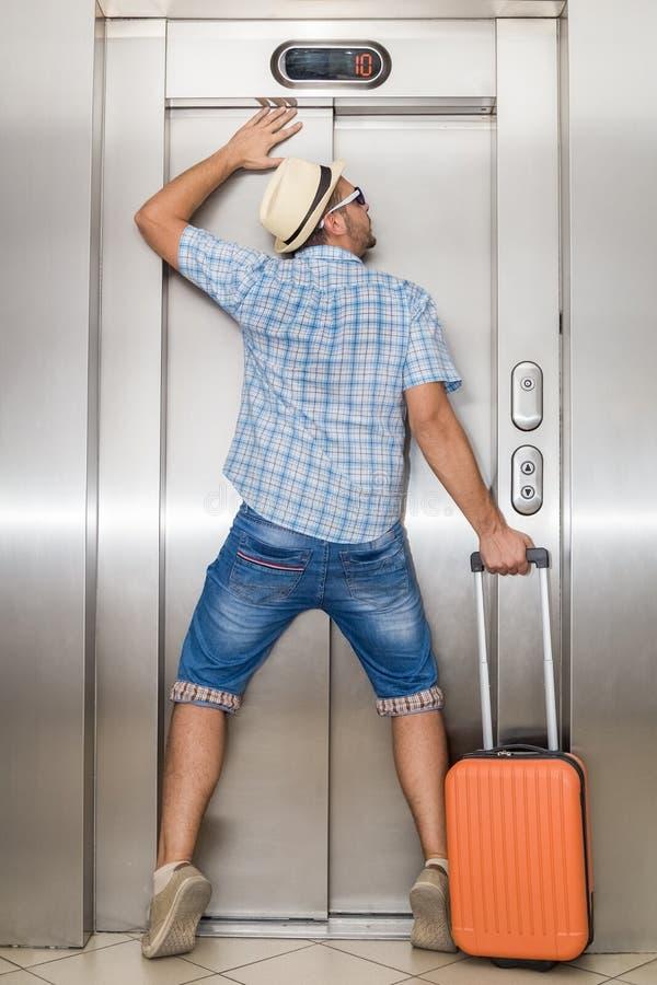 Il giovane uomo turistico non può uscire dell'elevatore fotografia stock