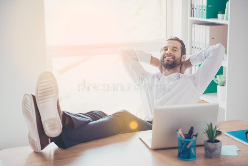Il giovane uomo vago bello sta sedendosi nel posto di lavoro che mette ciao immagine stock libera da diritti