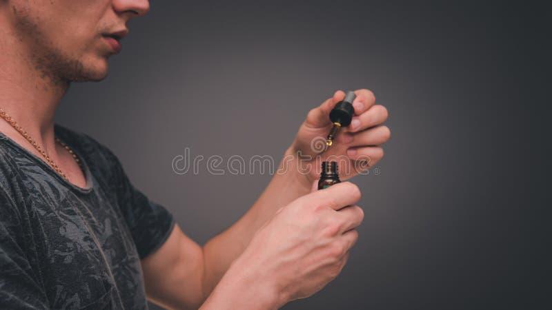 Il giovane usa l'olio di canapa La cannabis è un concetto di medicina di erbe immagini stock libere da diritti