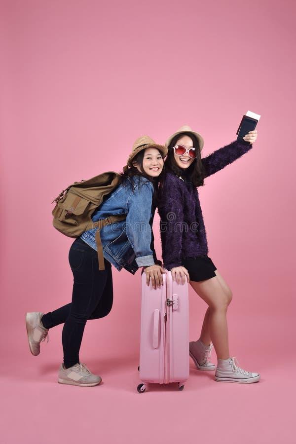 Il giovane viaggiatore asiatico con la valigia rosa gode della vacanza, amiche turistiche fotografia stock libera da diritti