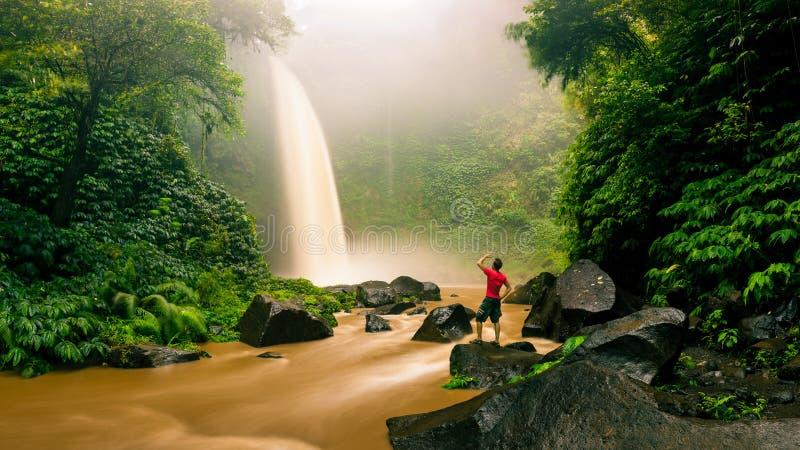 Il giovane viaggiatore dell'uomo forte gode della vista spettacolare di mattina, bella cascata di Nungnung fotografia stock libera da diritti