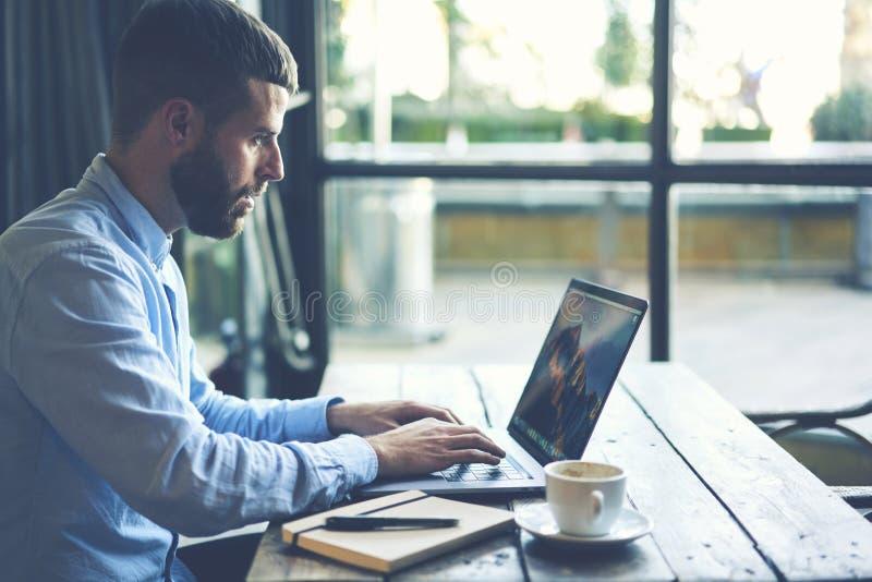 Il giovane viaggiatore di blogger dei pantaloni a vita bassa in un rivestimento del denim che scrive sulla tastiera del computer  fotografia stock