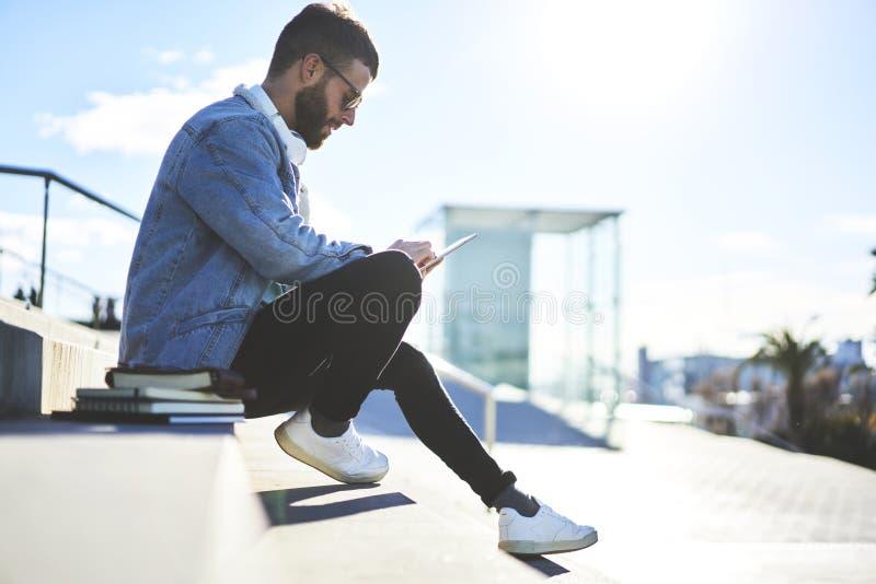 Il giovane viaggiatore di blogger dei pantaloni a vita bassa in un rivestimento del denim facendo uso del touchpad moderno e libe immagine stock libera da diritti