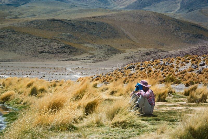 Il giovane viaggiatore femminile sta utilizzando il binocolo per vedere gli oggetti telecomandati fotografia stock