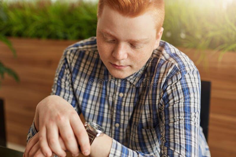 Il giovane vicecapo rosso alla moda si è vestito in ubicazione controllata della camicia in caffè accogliente che esamina il suo  fotografia stock libera da diritti