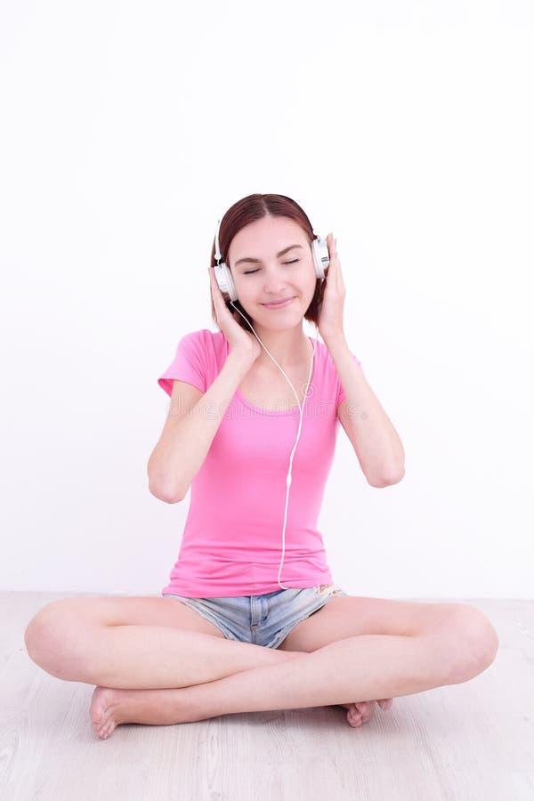 Il giovane womn si siede ascolta musica fotografia stock libera da diritti