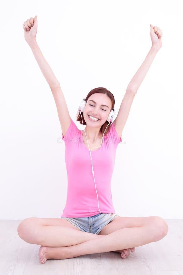 Il giovane womn si siede ascolta musica fotografia stock