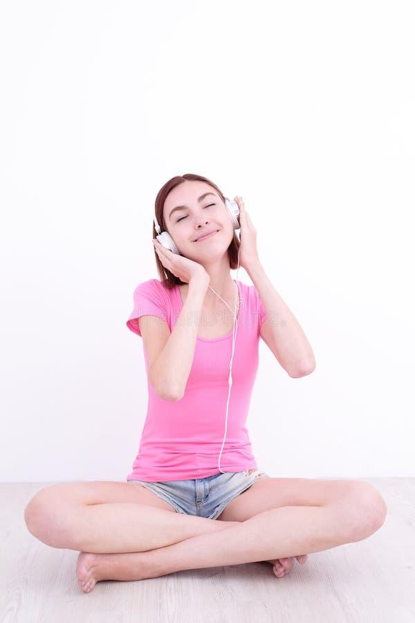 Il giovane womn si siede ascolta musica immagine stock