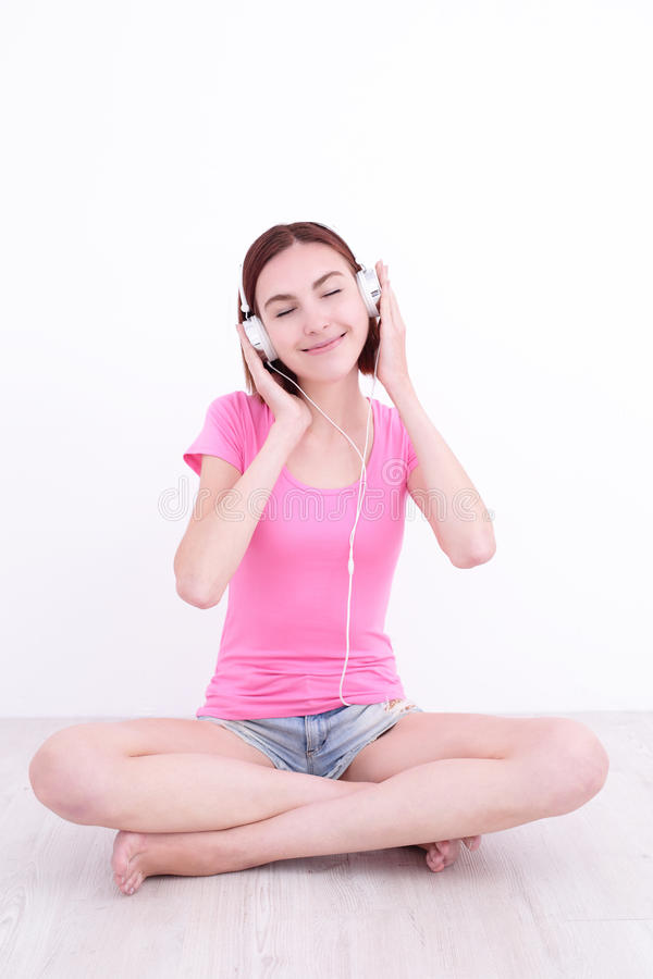 Il giovane womn si siede ascolta musica immagine stock libera da diritti