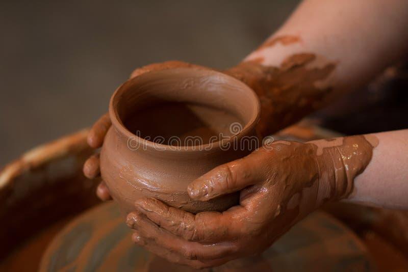 Il ` girante s del vasaio spinge ed articoli dell'argilla su preso da sopra Scolpisce le sue mani con una tazza dell'argilla Mani immagini stock