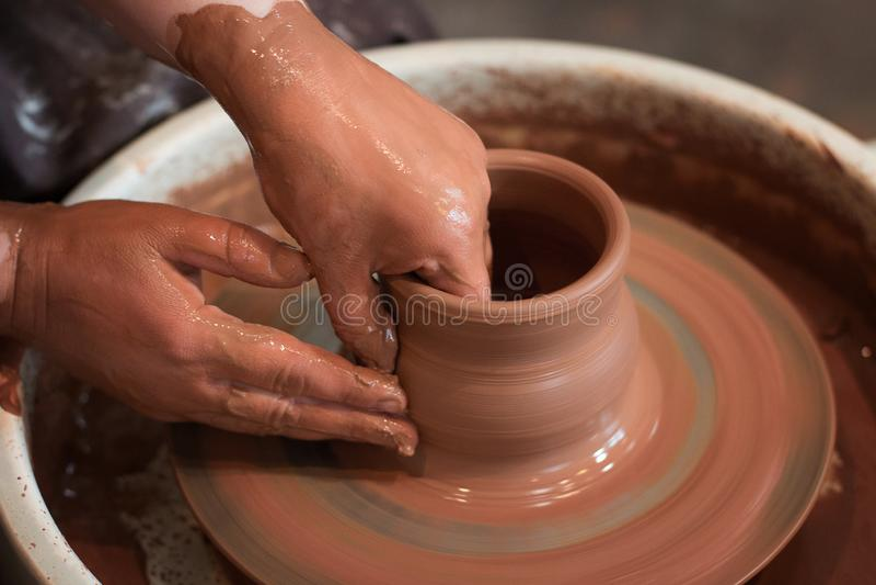 Il ` girante s del vasaio spinge ed articoli dell'argilla su preso da sopra Scolpisce le sue mani con una tazza dell'argilla su u immagini stock