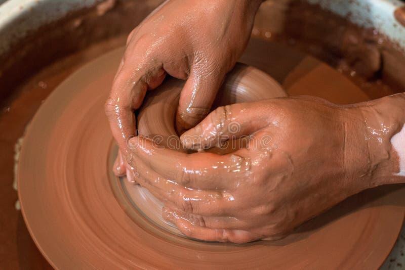 Il ` girante s del vasaio spinge ed articoli dell'argilla su preso da sopra Scolpisce le sue mani con una tazza dell'argilla su u fotografie stock