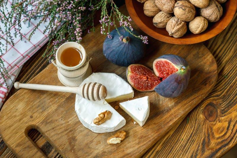 Il giro affettato del formaggio francese cremoso maturo e tenero del camembert è servito con i fichi, il miele e le noci rossi ma fotografie stock libere da diritti