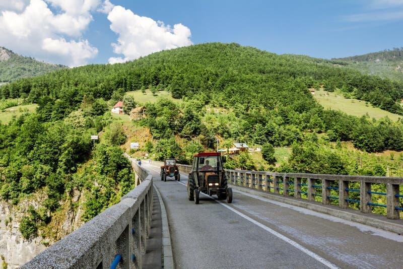 Il giro del trattore sul ponte di Dzhurdzhevich sopra il fiume T immagini stock
