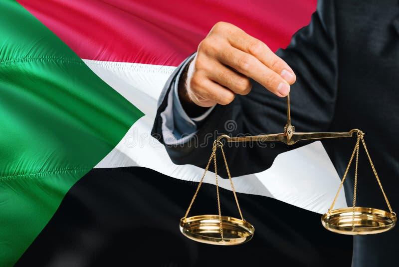 Il giudice sudanese sta tenendo la bilancia della giustizia dorata con il fondo d'ondeggiamento della bandiera del Sudan Tema di  fotografia stock libera da diritti