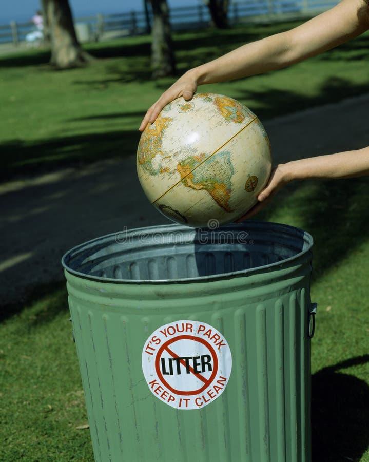 Il globo dentro cosegna il cestino residuo, fotografia stock