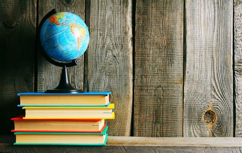 Il globo ed i libri multicolori immagini stock