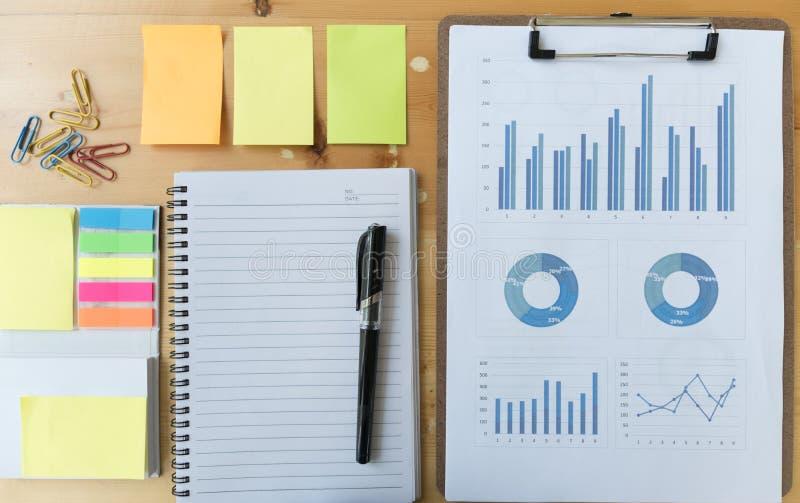 il grafico ed il grafico di vendita riferiscono con la penna, il taccuino, nota appiccicosa immagini stock