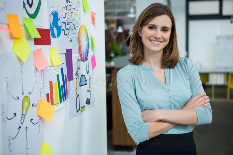 Il grafico femminile che sta con le mani ha attraversato in ufficio creativo fotografia stock libera da diritti