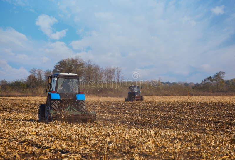 Il grande aratro blu del trattore due ha arato la terra dopo avere effettuato il raccolto del mais fotografia stock