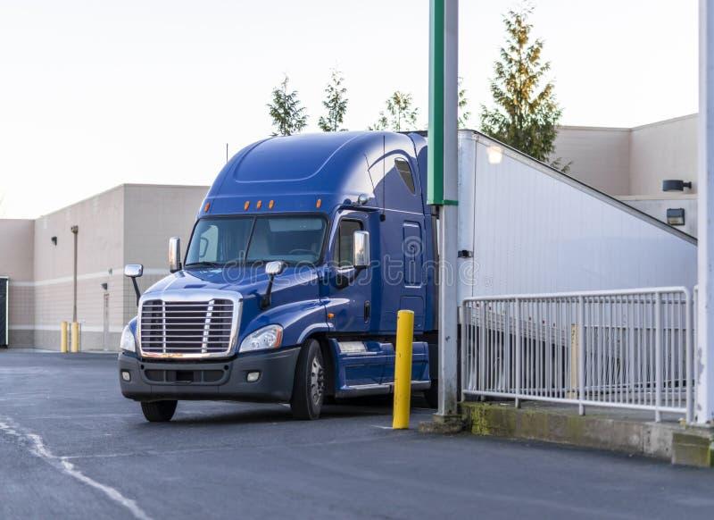 Il grande camion blu dei semi dell'impianto di perforazione con il rimorchio asciutto di van semi scarica le merci portate nel ba fotografie stock libere da diritti