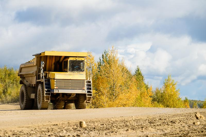 Il grande carrello di miniera giallo che trasporta i materiali si scola una strada non asfaltata fotografia stock